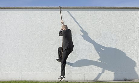 Businessman climbing over wall with rope
